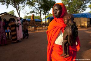 YIDA REFUGEE CAMP, SOUTH SUDAN - JUNE 29: A woman holds her grandson at a malnutrition and feeding center at the Yida refugee camp along the border with North Sudan June 29, 2012 in Yida, South Sudan. Yida refugee camp has swollen to nearly 60,000, as the refugees flee from South Kordofan in North Sudan. The rainy season has increased the numbers of sick children suffering from Diarrhea and severe malnutrition as the international aid community struggles to provide basic assistance to the growing population, most have arrived with only the clothes they are wearing. Many new arrivals walked from 5 days up to 2 weeks or more to reach the camp. (Photo by Paula Bronstein/Getty Images) ORG XMIT: 147399779